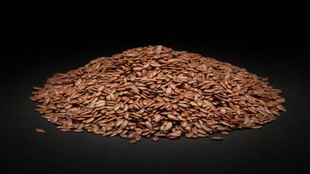linum usitatissimum: Pile of Organic Linseed or Flaxseed Linum usitatissimum on dark background. Stock Photo