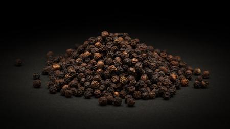 Pile of Organic Schwarzer Pfeffer Piper nigrum auf dunklem Hintergrund.