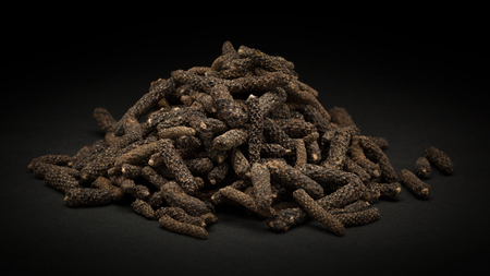 piper: Pile of Organic Long pepper Dried Fruit Piper longum on dark background.