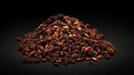 punica granatum: Pile of Organic Dried Pomegranate seeds Punica granatum on dark background. Stock Photo