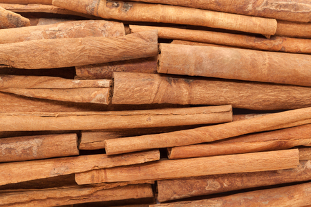 cinnamomum: Background of Raw Organic Cinnamon sticks (Cinnamomum verum). Stock Photo