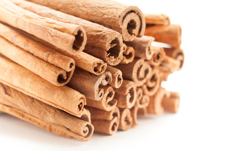 cinnamomum: Front side view of Raw Organic Cinnamon sticks (Cinnamomum verum) isolated on white background. Stock Photo