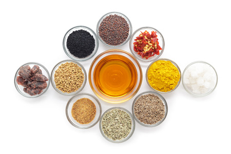 indian mustard: Different types of Indian spices with mustard oil in glass bowl isolated on white background. Top view. Stock Photo