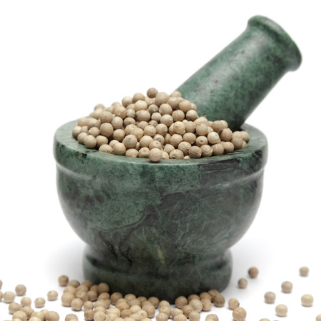 white pepper: Organic White Pepper (Piper nigrum) on marble pestle and over white background.