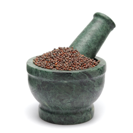 brassica: Organic Brown Mustard (Brassica juncea) on marble pestle. Isolated on white background.