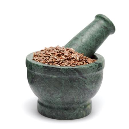 flaxseed: Organic Linseed or Flaxseed (Linum usitatissimum) on marble pestle. Isolated on white background. Stock Photo