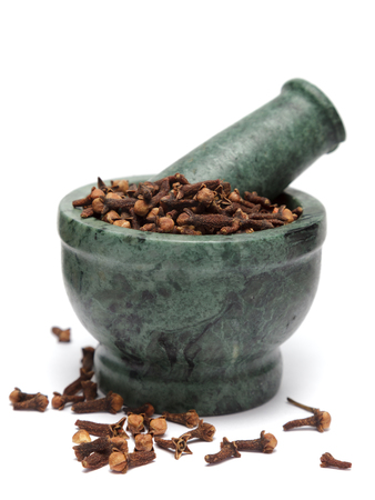 myrtaceae: Organic Indian Clove bud (Syzygium aromaticum) on marble pestle and over white background