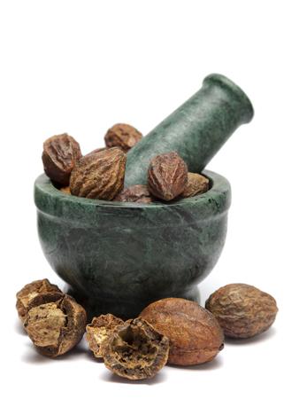 myrobalan: Organic Badi Harad fruit  (Terminalia chebula) on marble pestle and over white background.