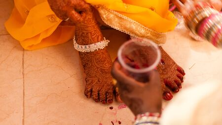 Bride feet coloring ceremony, a Hindu wedding ritual, during an Indian marriage. Stock Photo