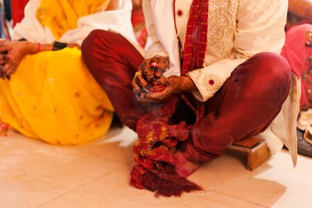 Bride and groom sitting together for puja, A typical Hindu wedding rituals during an Indian marriage. Stock Photo