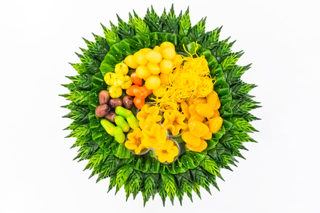 Thai dessert (Khanom Thai), colorful appearance and distinct flavors with handcraft of banana leaf on white background