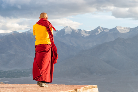 Indian tibetan monk lama in red and yellow color clothing standing in front of mountains Foto de archivo