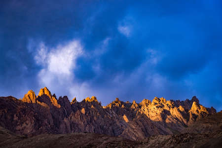enraged: Light and shadow on the top of mountain with cloudy sky