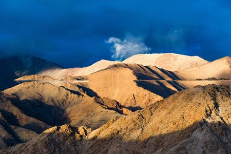 enraged: Light and shadow on the top of mountain with cloudy blue sky