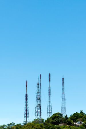 Telecommunication tower antenna and satellite dish on mountain with blue sky background