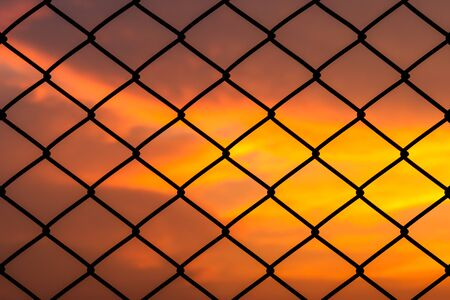 Metal mesh pattern with dramatic sky background Stock fotó - 129264995