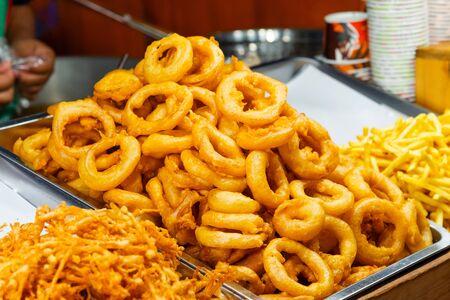 Rondelles d'oignon frites maison croustillantes dorées sur plateau au marché de l'alimentation de rue de Thaïlande Banque d'images