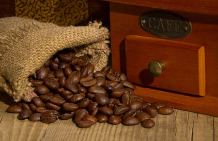 Wooden grinder with coffee beans on the tree with a bag photo