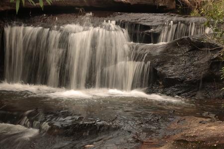 roo: Sang Chan or Moon light Waterfall (Nam tok long roo),: Water flows through a rock waterfall. Ubon ratchathani, Thailand  in rain Stock Photo
