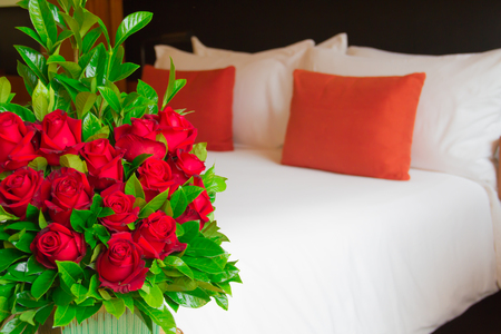 A vase full of red roses in vase on a wooden table against a background with a comfy bed   photo