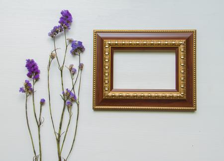 dried flower arrangement: statice purple flower on wooden floor background. With frame.