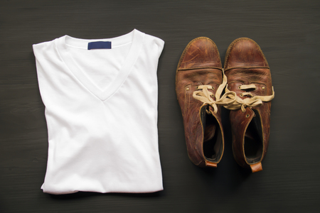 White T-shirt Brown leather shoes on a wooden floor. Stock Photo