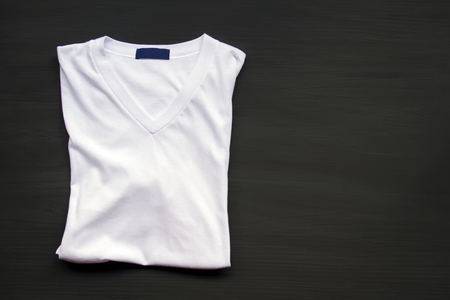 White T-shirt on a wooden floor. Stock Photo