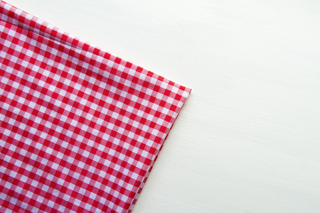 white colored wooden table with red squared textile tablecloth, top view, horizontal