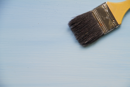 Paint brushes on a wooden blue background.