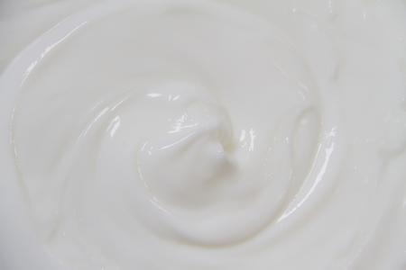 The white surface of the cream lotion softens the background. Archivio Fotografico - 119057513
