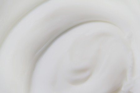 The white surface of the cream lotion softens the background. Archivio Fotografico - 119057527