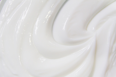 The white surface of the cream lotion softens the background. Archivio Fotografico - 119057539