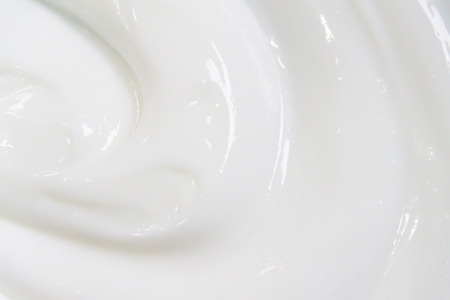 The white surface of the cream lotion softens the background. Archivio Fotografico - 119057545