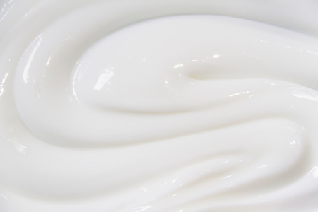 The white surface of the cream lotion softens the background. Archivio Fotografico - 119057576
