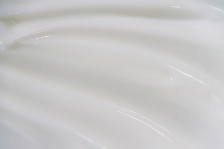 The white surface of the cream lotion softens the background. Archivio Fotografico - 119057584