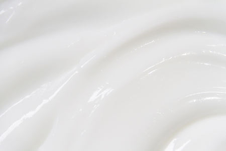 The white surface of the cream lotion softens the background. Archivio Fotografico - 119057591