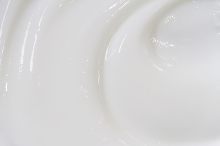 The white surface of the cream lotion softens the background. Archivio Fotografico - 119057592