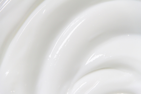 The white surface of the cream lotion softens the background. Archivio Fotografico - 119057595