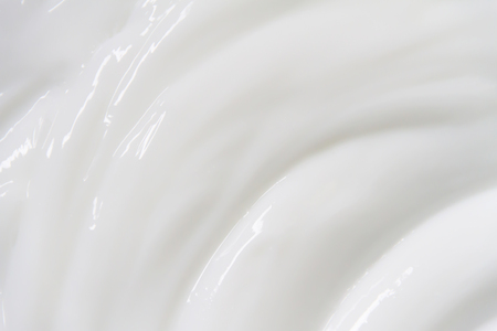 The white surface of the cream lotion softens the background. Archivio Fotografico - 119057602