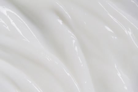 The white surface of the cream lotion softens the background. Archivio Fotografico - 119057643