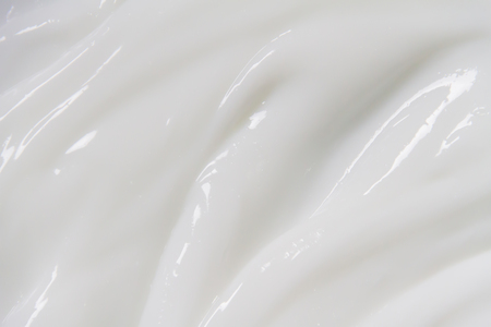 The white surface of the cream lotion softens the background. Archivio Fotografico - 119057644