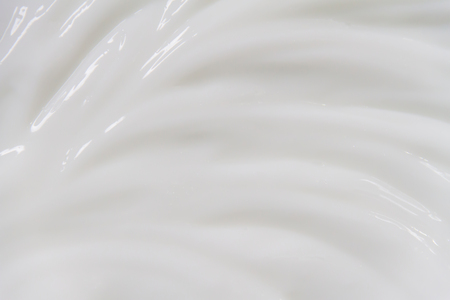 The white surface of the cream lotion softens the background. Archivio Fotografico - 119057648