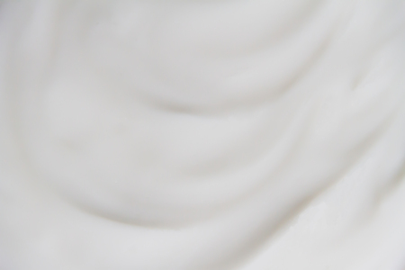 The white surface of the cream lotion softens the background. Archivio Fotografico - 119057766