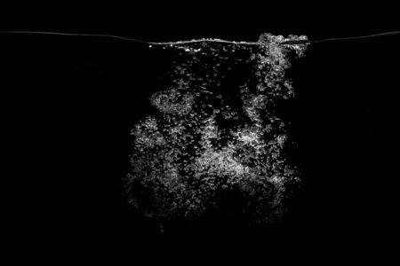 Underwater white bubbles on a black background.