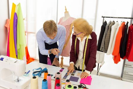 The female senior designer advises male customers to use the suit tailoring service.