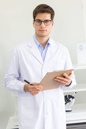 A young male scientist holding a research log in a laboratory