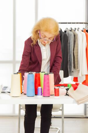 Professional female sewing designers in the office have a variety of fabric color schemes.