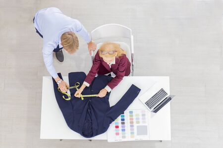 Topview Professional team work designers, young men and elderly women in the office with a variety of fabric tones and equipment for various designs.