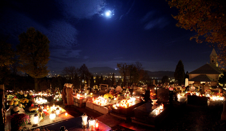 hallowmas: Candle flames illuminating  cemetery during All Saints Day Stock Photo