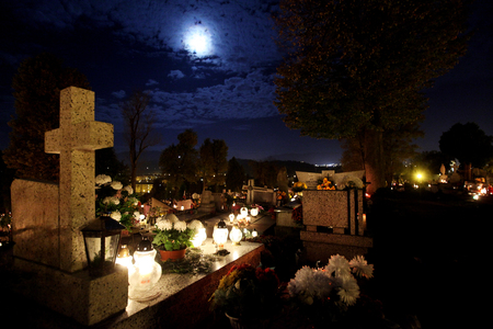 Candle flames illuminating  cemetery during All Saints Day